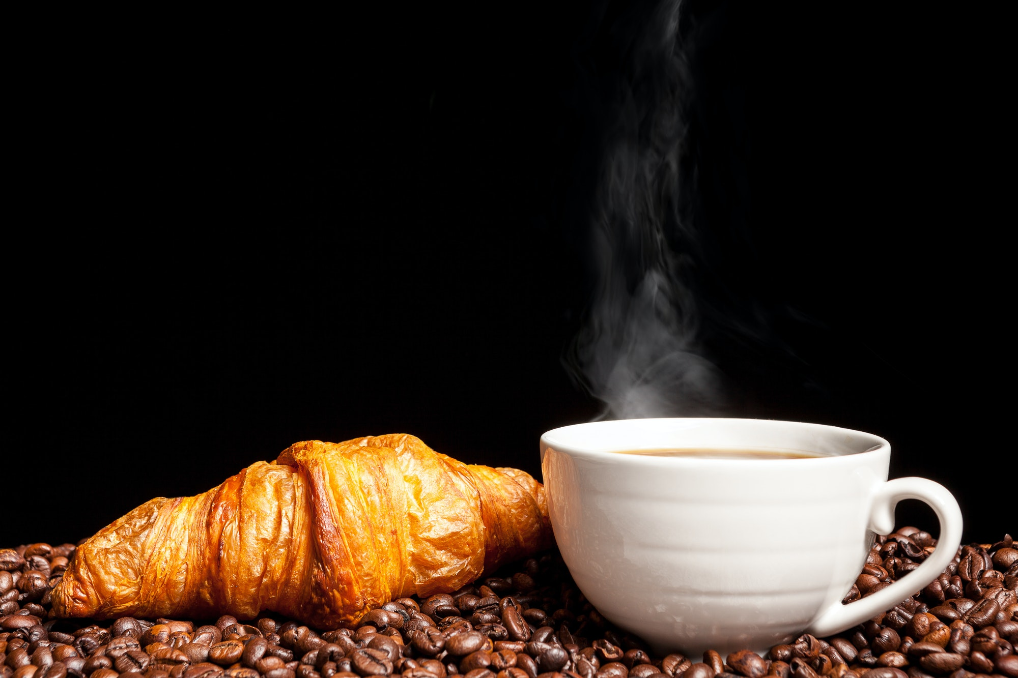 Croissant and steaming coffee beans in close up